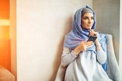 De moslim jonge slimme telefoon van het vrouwengebruik in koffie Stock Afbeelding