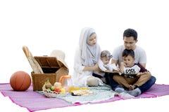 De moslimfamilie leest een boek in de picknick royalty-vrije stock afbeelding