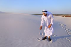 De moslimmens ontwikkelt zand langs wind die zich in midden van woestijn bevinden Royalty-vrije Stock Afbeelding