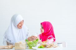 De moslimmoeder dient glas melk aan haar meisje en kijkt ook aan elkaar met het glimlachen, kom plantaardige salade op royalty-vrije stock afbeeldingen