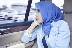 De moslimonderneemster kijkt peinzend in de auto stock fotografie