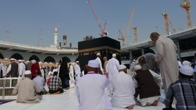 De moslimpelgrims bidden en circumambulate Kaaba stock footage