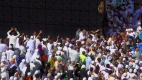 De moslimpelgrims slepen aan kus Zwarte Steen mee in Masjidil Haram in Makkah, Saudi-Arabië stock video