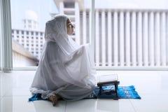 De moslimvrouw bidt thuis aan Allah royalty-vrije stock fotografie