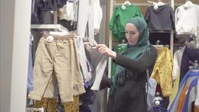 De moslimvrouw in een hijab en een rugzak kiest kleren in een opslag van kinderen stock video