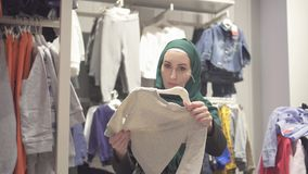 De moslimvrouw in een hijab en een rugzak kiest kleren in een opslag van kinderen in een winkelcentrum stock videobeelden