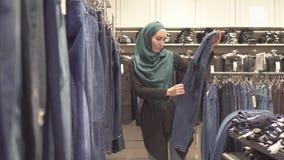 De moslimvrouw in hijab en een rugzak kiest jeans bij de opslag in de wandelgalerij stock footage