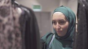 De moslimvrouw in hijab kiest een kleding in de opslag, close-up stock videobeelden