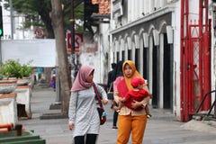 De moslimvrouw Indonesi?r vervoert kinderen en het lopen op het voetpad naast de weg bij oude stadsbuurt in Djakarta royalty-vrije stock afbeelding