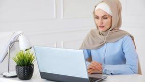 De moslimvrouw leert het Engels in oortelefoons online gebruikende computer royalty-vrije stock foto's