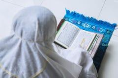 De moslimvrouw leest Quran tijdens ramadan tijd Stock Afbeelding