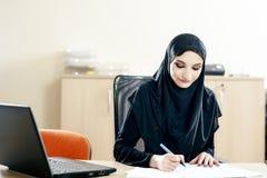 De moslimvrouw vult de documenten Stock Fotografie