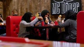 De moslimvrouwen eten in een snel voedselrestaurant stock videobeelden