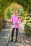 De motie is geluk Vrouw met fiets in bloeiende tuin Weekendactiviteit Actieve vrije tijd en levensstijl Meisjesrit stock afbeelding