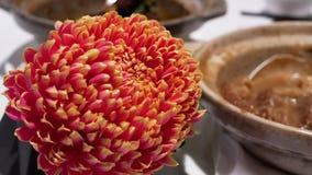 De motie van hete thee en de bloem op lijst en onduidelijk beeldmotie van mensen genieten van maaltijd stock video