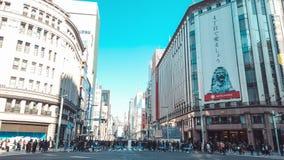 de Motietime lapse die van 4K UHD van Ginza 4-Chome met overvol mensen en autoverkeer kruisen over de wegverbinding stock footage