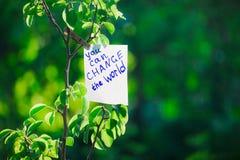 De motiverende uitdrukking u kan de wereld veranderen Op een groene achtergrond op een tak is een Witboek met een motiverende uit stock fotografie