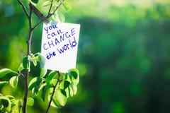 De motiverende uitdrukking u kan de wereld veranderen Op een groene achtergrond op een tak is een Witboek met een motiverende uit royalty-vrije stock foto