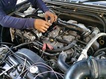 De motor van de autodienst, reparatie, controle op onderhoud, auto mechanische mens haalde klep onder kapauto aan, mensenhand het stock fotografie