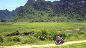 De motor van de paarrit langs grondweg voorbij kleine rivier stock video