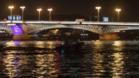 De motorboot drijft de rivier in nachtstad voor brug stock video