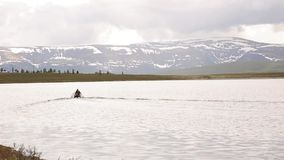 De motorboot drijft op een bergmeer die, die en in de bergen wandelen vissen stock videobeelden