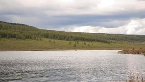 De motorboot drijft op een bergmeer die, die en in de bergen wandelen vissen stock video