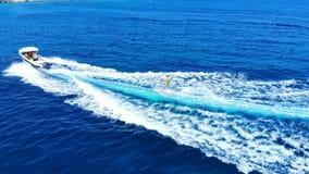 De motorboot en de wateren ski?ende mens draaiden zich, satellietbeeld om stock footage