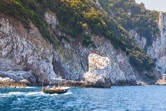 De motorboot gaat dichtbij rotsen van Capri-eiland, Italië Stock Foto's