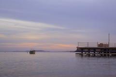 De motorboot wordt verankerd onder de Baai, die zonsondergang op beac gelijk maken Royalty-vrije Stock Afbeeldingen