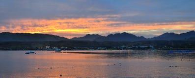 De motorboot wordt verankerd onder de Baai, die zonsondergang op beac gelijk maken Stock Fotografie