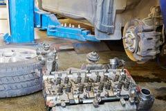 De motorcilinderkop en het autowiel liggen op vloer Royalty-vrije Stock Foto's