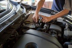 De motoringenieur vervangt autobatterij omdat de autobatterij wordt uitgeput stock afbeeldingen