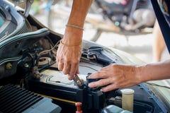 De motoringenieur vervangt autobatterij omdat de autobatterij wordt uitgeput royalty-vrije stock afbeeldingen