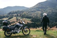 De motorrijder kijkt aan afstand met zijn toeristische motorfiets, met grote zakken klaar voor een lange reis, zwarte stijl, witt stock afbeelding