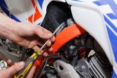 De motorrijder vervangt, controleert de gloedstop in een motorfiets royalty-vrije stock foto
