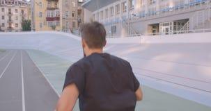 De mouvement portrait de vue de retour du coureur masculin sportif caucasien adulte pulsant sur le stade dans la ville urbaine de banque de vidéos