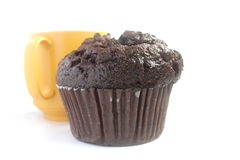 De muffin van de chocolade en gele kop op witte achtergrond Stock Afbeelding