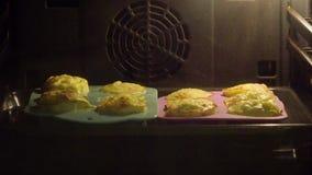 De muffins in de oven, in siliconevorm, het deeg neemt onder de invloed van een hoge graad toe stock video