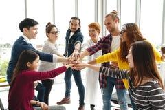 De multi-etnische jonge handen van de teamstapel samen als vertrouwd op eenheid en groepswerk in modern bureau royalty-vrije stock afbeelding