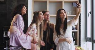 De multi etnische mooie dames met een mooie glimlach nemen selfies met een smartphone in pyjama's in een stedelijke ontwerpstudio stock footage