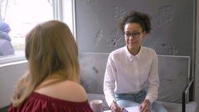 De multi-etnische verhouding, mooi Afrikaans Amerikaans tienermeisje in gebrild communiceert met meisje en schrijft stock footage