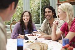 De multi-etnische Vrienden die bij Veranda genieten van dienen in stock foto