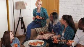 De multi-etnische vrienden eten thuis pizza en bespreking stock video
