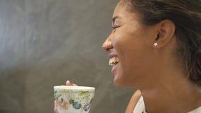 De multi rassenvrouw zit en drinkt kop thee of koffie stock videobeelden