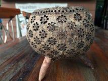 De multifunctionele houder maakte van shell van de kerfkokosnoot, het ontwerp van het bloempatroon, op de houten lijst royalty-vrije stock afbeeldingen