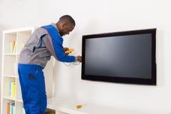 De Multimeter van elektricienchecking television with royalty-vrije stock foto's