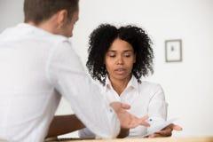 De multiraciale collega's die bedrijfstatistieken bespreken tijdens komen samen stock afbeeldingen