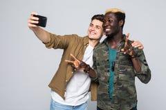 De multiraciale die vrienden nemen selfie op telefoon op witte achtergrond wordt geïsoleerd Twee internationale vrienden stedents stock foto