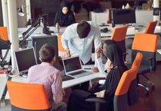 De multiraciale eigentijdse bedrijfsmensen die verbonden aan technologische apparaten zoals tablet en laptop werken stock foto